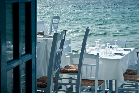Restaurant tables on the sea in a Greek village   Stock Photo