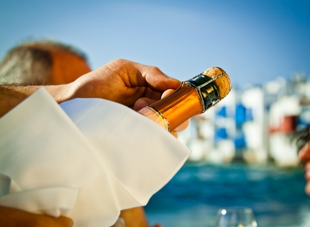 Popping a bottle of champagne open by the sea