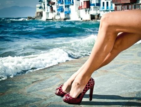Sexy summer legs in high heels by the sea in Mykonos, Greece. Stock Photo