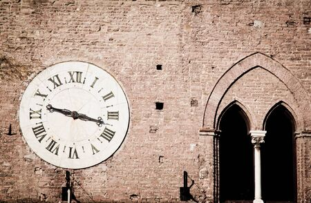 Ancient wall clock on the outside of a medieval palace in Siena, Italy, that used be a hospital and is now a museum   photo