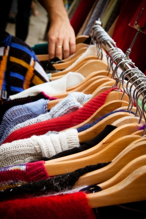 A rack of second-hand jumpers and cardigans at a market in London  recession bargains  Hand of someone browsing visible in the background  photo