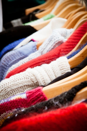 clothing rack: Close-up on a rack of second-hand jumpers and cardigans at a market in London  recession bargains