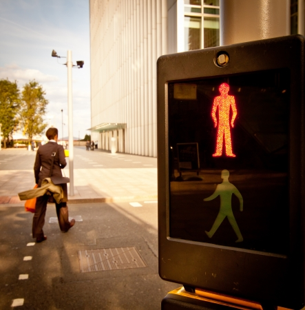 pedestrian crossing: A businessman rushing through the red light at a pedestrian crossing in Canary Wharf
