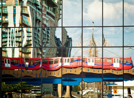 A Docklands Light Railway train reflected on the glass surface of an office block in Canary Wharf  The sails of a tallship docked in West India Quay are also reflected on the right  photo