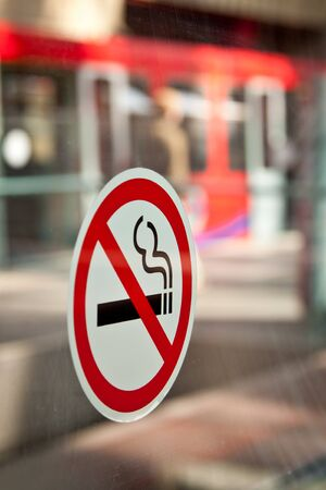 No Smoking sticker in a DLR station in London, Docklands  Red train in the background  Portrait orientation   photo