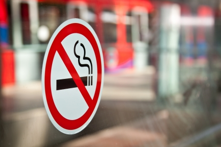anti tobacco: No Smoking sticker in a DLR station in London, Docklands  Red train in the background