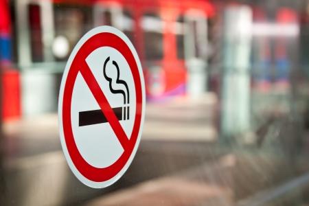 prohibido fumar: Sin etiqueta de consumo de tabaco en una estaci�n de DLR en Londres, Docklands Red de tren en el fondo