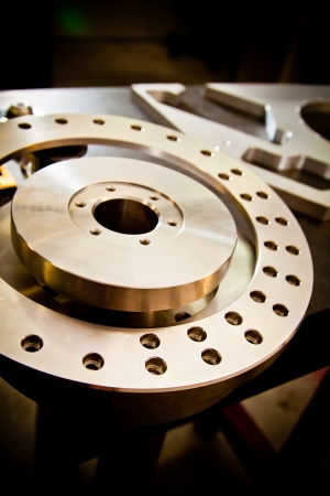 Custom-milled machine part made with CNC machine. Focus on foreground. photo