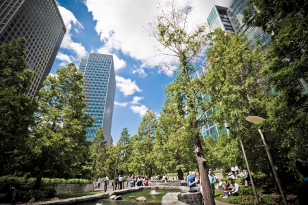 canary wharf: London, 3 June 2011: office workers enjoying the gorgeous summer weather at lunchtime, in Londons financial district at the Docklands. Jubilee Park, Canary Wharf, Docklands, London. Landscape orientation. Editorial