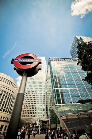 commuters: London, 3 June 2011: Underground sign in Canary Wharf, Docklands, Londons financial district. One Canada Square, the tallest completed building in the UK, in the background on the right, Reuters building on the left.  Editorial