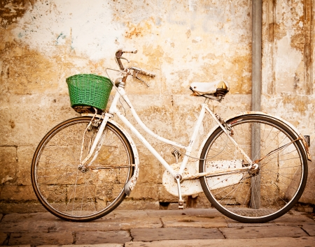 An old, rusty white bicycle with a basket leaning against a grungy wall in Italy