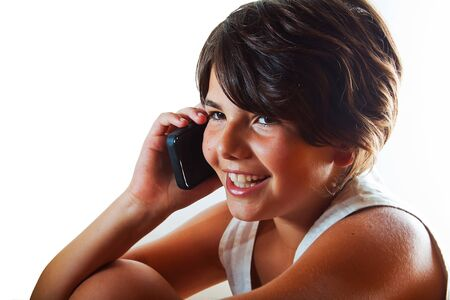 Smiling teenage girl having a conversation on her smartphone. Isolated against white background. Plenty of copyspace. photo