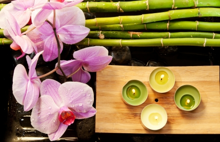 Spa scene with pink orchids covered in dew, bamboo, candles and pebbles  Focus on the orchid