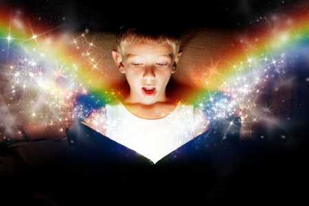 A little boy opening a magic book  Concept that lends itself to express the magic of fairytales, Christmas, or education   Standard-Bild