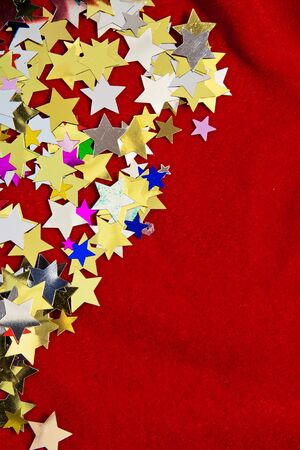 christmas motif: Colourful, glittering stars on red velvet background  Christmas wishes or birthday message  Plenty of copy space