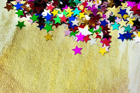 Colourful, glittering stars on gold background  Christmas wishes or birthday message  Plenty of copy space  photo