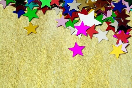 Close up on colourful, glittering stars on gold background  Christmas wishes or birthday message  Plenty of copy space  photo