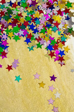 Colourful, glittering stars on gold background  Christmas wishes or birthday message  Plenty of copy space, portrait orientation  photo