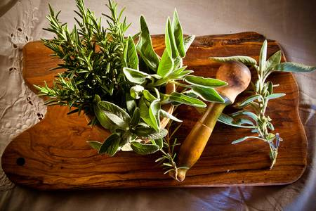 pestel: Old and weathered pestel and mortar on a wooden board, full of fresh rosemary and sage ready to be crushed