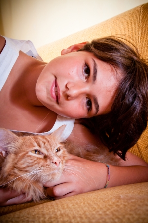 A young girl with her long-haired ginger cat  photo