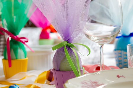 tulle: Colorful Easter table setting with beautiful crockery, eggs, ribbons. Shallow depth of field, focus on the green ribbon. Stock Photo