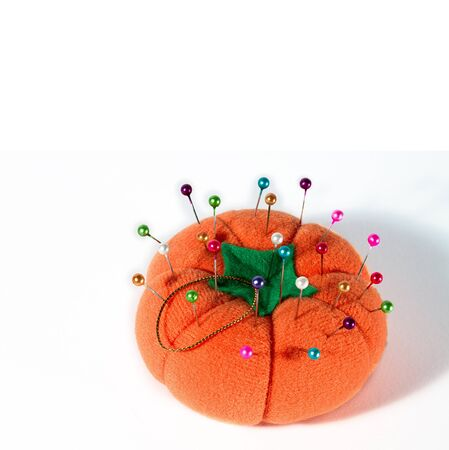 Colorful pins on pin cushion against white background, seen from above   photo