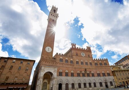 Piazza del Campo, Siena on a spring day, with the sun peeking in from the tower and forming a starburst. photo