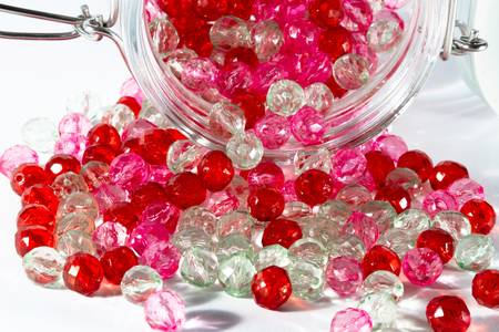 haberdashery: Jar full of a pink, red and clear beads for haberdashery  Landscape orientation  Stock Photo