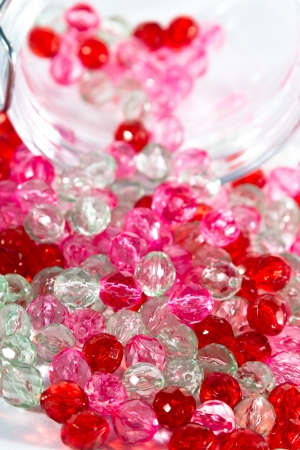 portrait orientation: Jar full of a pink, red and clear beads for haberdashery  Portrait orientation  Selective focus