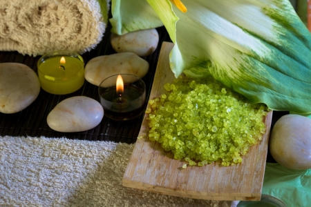 Green bath salts with candles and a beautiful calla lily: spa scene, relaxation, wellness concept. photo