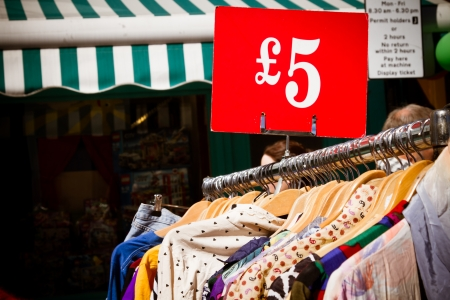 bargain for: Bargain for a fiver: second-hand clothes for sale at market. Recession theme.