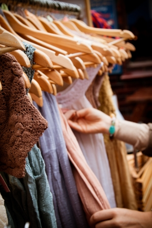 junk yard: Recession bargains: rack of second-hand dresses for sale at market. Portrait orientation. Stock Photo