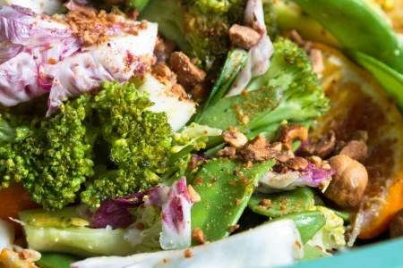 Healthy diet: colorful broccoli salad with oranges, mangetout beans, red radicchio and nuts. photo