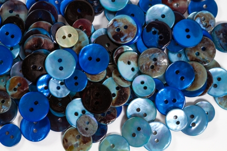 customise: CLose-up on mother-of-pearl blue buttons against a white background.