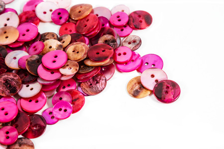 customise: PInkand red mother-of-pearl buttons against a white background. Plenty of copy space.
