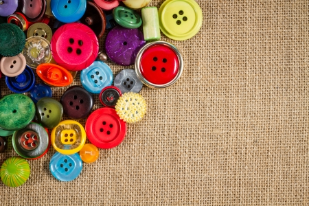 customise: A great variety of colorful vintage buttons against a fabric background. Plenty of copy space.