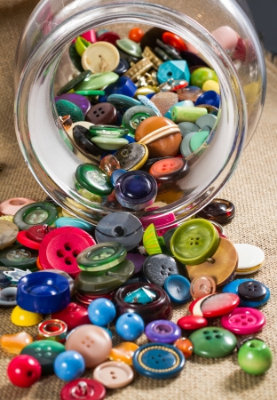 portrait orientation: A great variety of colorful vintage buttons spilling out of a jar, against a fabric background. Portrait orientation. Stock Photo