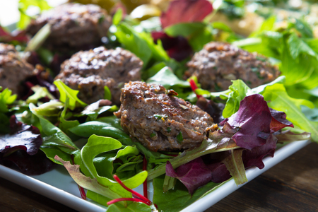 salad greens: Middle East cuisine: a plate of delicious lamb burgers, olives and hummus.