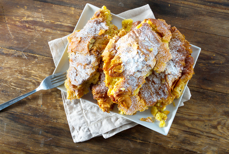 french cafe: Continental breakfast: delicious almond croissants sprinkled with icing sugar and with a custard fillin, on a rustic wooden background. Stock Photo