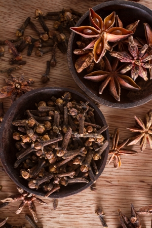 Assorted spices for food and decoration: star anise and cloves, against a wodden background.