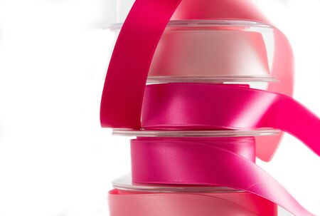 organza: Stack of reels of satin ribbon in all shades of pink. On white background.