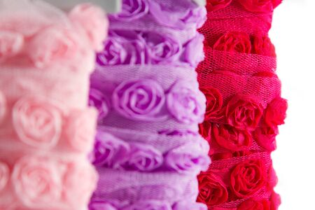 organza: Pretty ribbons with rose patterns in a light mesh material. focus on the red reel in the background.