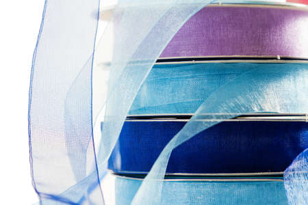 organza: Stack of reels of gauze ribbon in all shades of blue. On white background. Stock Photo