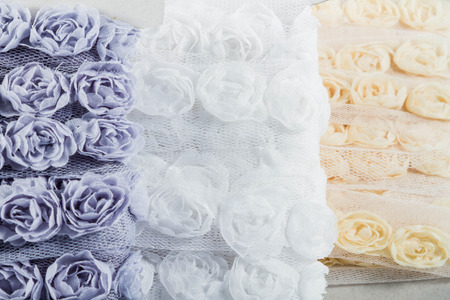 organza: Pretty ribbons with rose patterns in a light mesh material. Focus on the white roses in the middle ground. Stock Photo