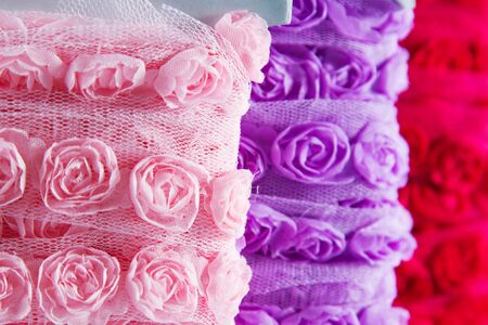 Pretty ribbons with rose patterns in a light mesh material. Focus on the pink reel in the foreground. photo