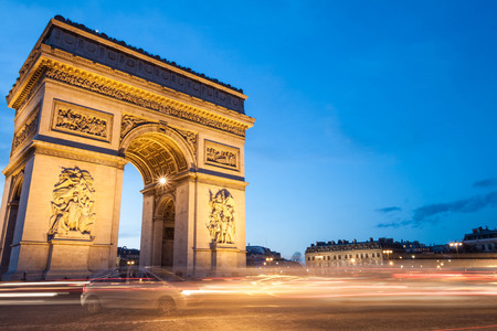 The Arc de Triomphe in Paris, France, at twilight with traffic light trails.