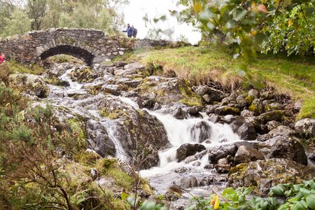 lake district england: A beautiful waterfall by an old bridge in the Lake District, England. Misty weather. Stock Photo