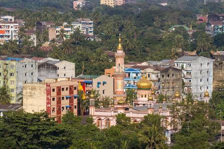 urban jungle: Jungla urbana. un paisaje urbano de Yangon con edificios antiguos, una mezquita y un mont�n de palmeras y vegetaci�n. Foto de archivo