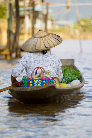 floating market: Woman carrying her vegetables to sell at a floating market on Inle Lake, Myanmar (Burma). Stock Photo