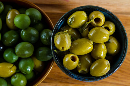pitted: Lovely, juicy, fat olives from the Mediterranean, in rustic bowl. Stock Photo